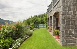 Casa de piedra, jardín Imágenes de archivo libres de regalías