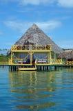 Casa de planta baja tropical sobre el agua con el tejado cubierto con paja Imagen de archivo