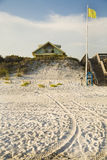 Casa de playa con la escalera de madera, la bandera amarilla, y las pisadas del neumático en arena Foto de archivo libre de regalías