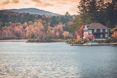 Casa de playa en el lago largo, Adirondacks, NY, en la caída rodeado por el follaje fotos de archivo libres de regalías