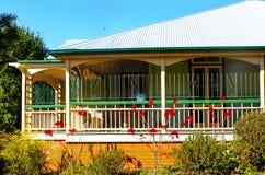 Casa de Queensland con las barras de metal adornadas en el abrigo alrededor del pórtico, del tejado del metal y de los poinsettas Fotos de archivo libres de regalías