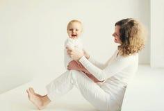 Casa de sorriso feliz da mãe e do bebê na sala branca Fotografia de Stock