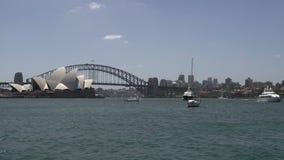 Casa de Sydney Opera con el puente del puerto con los barcos delante de él metrajes