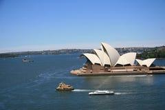 Casa de Sydney Opera con la ciudad del fondo Imagenes de archivo