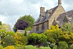Casa de tejado cubierto con paja con el jardín en la floración en pueblo inglés idílico Fotografía de archivo