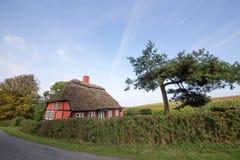 Casa de tejado cubierto con paja roja Imágenes de archivo libres de regalías