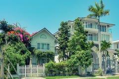 Casa de tres pisos hermosa del Ne con las palmeras, los árboles, y diseño del paisaje en el verano fotos de archivo libres de regalías
