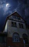Casa de Víspera de Todos los Santos con la luna y los palos Foto de archivo libre de regalías
