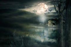 Casa de Víspera de Todos los Santos con la luna y los palos Fotos de archivo