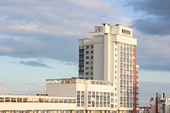 Casa de varios pisos del nuevo bloque moderno en fondo azul marino del cielo en cuatro colores: rojo, anaranjado, gris y blanco N Fotografía de archivo