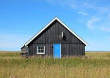 Casa de verão com as pranchas de madeira pretas e a porta azul Imagens de Stock Royalty Free