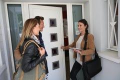 Casa de visita dos pares a comprar com corretor de imóveis fotografia de stock royalty free