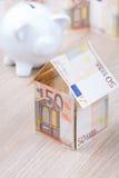Casa del billete de banco con la hucha Foto de archivo