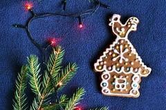 Casa del biscotto del pan di zenzero su fondo blu, ramo attillato, Ch Immagine Stock