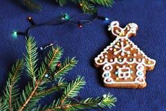 Casa del biscotto del pan di zenzero su fondo blu, ramo attillato, Ch Fotografia Stock