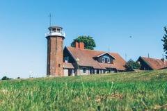 Casa del campo en césped verde con el cielo azul fotos de archivo