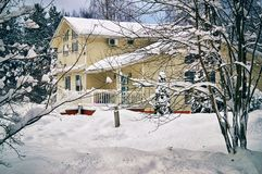 Casa del campo rodeada por los árboles cubiertos pesadamente con nieve en enero Foto de archivo libre de regalías