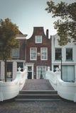Casa del canal en cerámica de Delft y puente blanco hermoso en el Voorstraat imagen de archivo libre de regalías