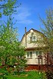Casa del jardín rodeada por los árboles florecientes Fotos de archivo