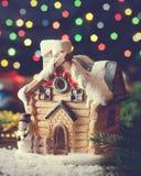 Casa del juguete de la Navidad en fondo del bokeh de la guirnalda Imagen de archivo libre de regalías