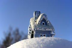 Casa del juguete de la Navidad en la nieve acumulada por la ventisca Imagen de archivo libre de regalías