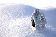 Casa del juguete de la Navidad en la nieve acumulada por la ventisca Foto de archivo libre de regalías
