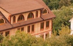 Casa del ladrillo entre los árboles Fotos de archivo libres de regalías