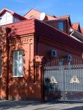 Casa del ladrillo rojo con la entrada cercada Foto de archivo