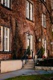 Casa del ladrillo rojo con un pórtico entrelazado con las vides secas imagenes de archivo