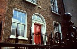 Casa del mattone con il portello rosso Fotografia Stock Libera da Diritti
