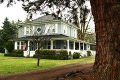 Casa del paese con l'avvolgere largo intorno al portico fotografia stock