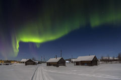Casa del pueblo en las luces de la luna y del aurora borealis imagen de archivo libre de regalías