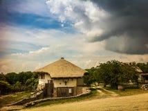 Casa del villaggio e tempesta d'avvicinamento Fotografia Stock