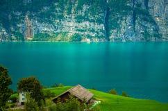 Casa del villaggio vicino al lago Walensee ed alla catena di montagna, Svizzera immagini stock libere da diritti