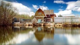 Casa del villaggio vicino allo stagno di riflessione Fotografia Stock Libera da Diritti