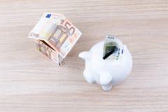 Casa della banconota con il porcellino salvadanaio Fotografie Stock