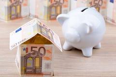 Casa della banconota con il porcellino salvadanaio Immagine Stock