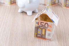 Casa della banconota con il porcellino salvadanaio Immagini Stock