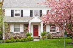 Casa della famiglia con il prato inglese di fronte in primavera fotografie stock