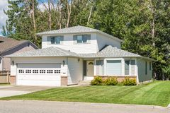 Casa della famiglia con l'iarda anteriore abbellita il giorno soleggiato in Columbia Britannica immagine stock libera da diritti