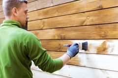 Casa della pittura del lavoratore esteriore con colore protettivo di legno immagini stock