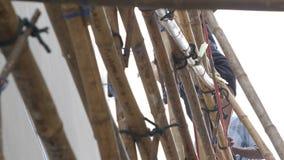 Casa della pittura del lavoratore mentre stando sull'impalcatura di bambù stock footage