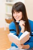 Casa della ragazza dell'adolescente - allievo felice con il libro Fotografia Stock