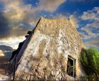 Casa destruida bajo los cielos dramáticos de la puesta del sol Foto de archivo