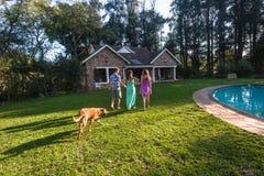 Casa di camminata del cane del ragazzo delle ragazze Fotografie Stock Libere da Diritti