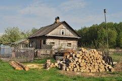 Casa di campagna con il mucchio di legna da ardere Fotografia Stock