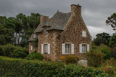 Casa di campagna medievale favolosa incantante in una campagna con un alto tetto e le finestre con gli otturatori bianchi con un  fotografia stock libera da diritti