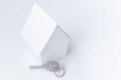 Casa di carta e chiave su bianco, fondo dello spazio della copia Immagini Stock