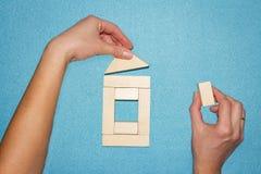 Casa di configurazione delle mani dei cubi su fondo blu Concetto della costruzione e di assicurazione Camera fatta dei blocchi di fotografia stock libera da diritti