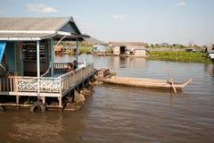 Casa di galleggiamento solida con un portico enorme e bambini che si siedono all'ombra del tetto e della barca legati alla soglia Fotografie Stock Libere da Diritti
